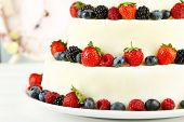 Beautiful wedding cake with berries on wooden table, on light background