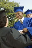 Graduate shaking hand of dean outside low angle view
