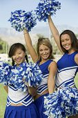 Cheerleaders waving blue and white pom-poms (portrait)
