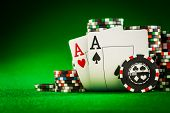 picture of poker hand  - Stack of chips and two aces on the table on the green baize  - JPG