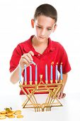Jewish boy using the shamash candle to light the menorah for Hanukkah.