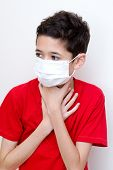 A sick young boy clutches his throat with face mask on.
