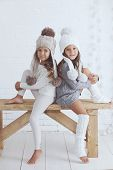 foto of leg warmer  - Cute little girls of 5 years old wearing knitted trendy winter clothes posing over white brick wall - JPG