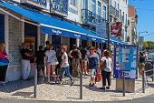 Lisbon, Portugal. August 24, 2014: The famous Pasteis de Belem - Egg Custard Tart - pastry shop in Lisbon. Clients wait on the street as the shop is always full. Over 20.000 tarts are sold daily.