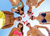 friendship, christmas, summer vacation, holidays and people concept - group of smiling friends wearing swimwear and santa helper hats standing in circle over blue sky