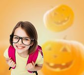 education, holidays, childhood, vision and people concept - smiling little girl in glasses over halloween pumpkins background