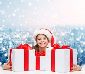 holidays, presents, christmas, childhood and people concept - smiling girl in santa helper hat with gift boxes over snowing city background