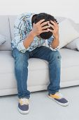 Tensed football fan sitting on couch with head in hands