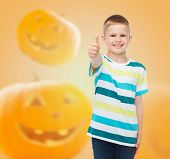 holidays, childhood, happiness, gesture and people concept - smiling little boy showing thumbs up over halloween pumpkins background