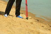 Active Woman Senior Nordic Walking On A Beach. Legs