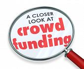 Crowd Funding words under a magnifying glass for a closer look at investing through internet websites to fundraise campaign for your new project