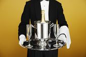 Waiter delivering champagne on silver platter