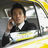 Businessman talking on cell phone in cab