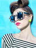 Face close up of beautiful young woman wearing stripy sunglasses
