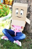 Woman with cardboard box on her head with sad face, holding flower, outdoors