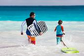 Father and son running towards ocean with boogie boards having fun on beach vacation