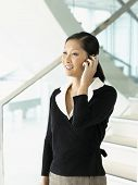 stock photo of people talking phone  - Smiling businesswoman standing talking on mobile phone - JPG