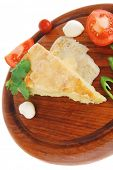 dairy food : cheese casserole piece over wood plate served with peppers , tomatoes and chives isolat