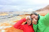 Iceland funny tourists couple having fun taking selfie photo with at landmark destination: Namafjall Hverarondor hverir mudpot also called mud pool hot spring or fumarole. Smell from sulfur on volcano poster