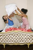 stock photo of pillow-fight  - Teenage Girls pillow fighting kneeling on funky bed - JPG