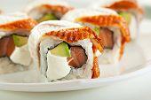 Roll made of Fresh Salmon, Smoked Eel, Cream Cheese and Avocado inside. Smoked Eel outside
