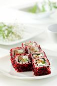 Maki Sushi - Roll made of Cream Cheese, Jjapanese omelet, Cucumber and Smoked Eel inside. Red and Black Tobiko outside