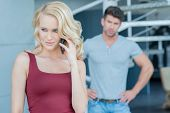 Beautiful young blond woman talking on her mobile phone watched by her husband standing with his hands on his hips