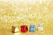 Small decorative colorful presents on glitter background