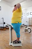 impressed overweight woman standing on scales in the gym