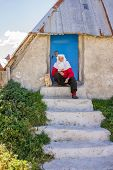 Portrait of very elderly woman in front of her home in village