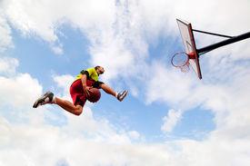 foto of slam  - Young man jumping and making a fantastic slam dunk playing streetball - JPG