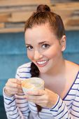 Young woman having a cappuccino at the cafe