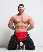 muscular construction worker in overalls. kneeling