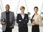 Interracial team of businesspeople standing for portrait in business hallway, smiling.