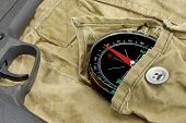 picture of handguns  - Modern Handgun and Compass On The Weathered Backpack - JPG
