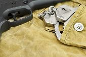 stock photo of handcuff  - Black Handgun and Handcuffs On The Weathered Backpack - JPG