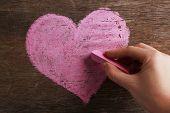 Hand draws heart on blackboard
