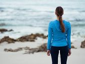 Sporty young woman standing in front of the ocean