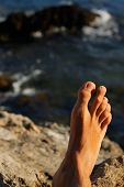 Man Feet Relaxing On Holidays In A Beach Or Lake With The Sea Water In The Background