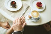 hands of bride and groom on table with cakes and cup of cappuccino