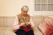 picture of grandmother  - Portrait of grandmother knitting with red wool and sitting on the couch - JPG