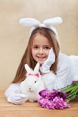 Cute bunnies with spring flowers - little girl with bunny ears and white rabbit- shallow depth of field