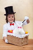 Happy magician boy conjuring an easter rabbit and colorful eggs into a basket- shallow depth of field
