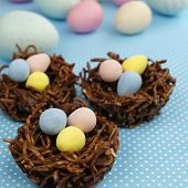 Chocolate Nests Filled With Easter Eggs On Blue