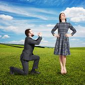 crying man looking at beautiful woman and asking for forgiveness. photo at outdoor