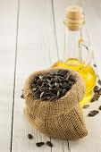 sunflower oil and seeds on wooden background