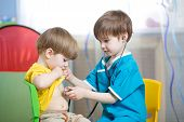 stock photo of home remedy  - children boys play doctor together at home - JPG