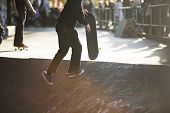 picture of skate board  - Skateboarder carrying a board in a skate park
