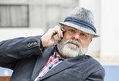 Attractive Old Man With Beard And Hat Talking On Phone