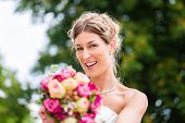 Wedding bride with bridal bouquet outside at garden